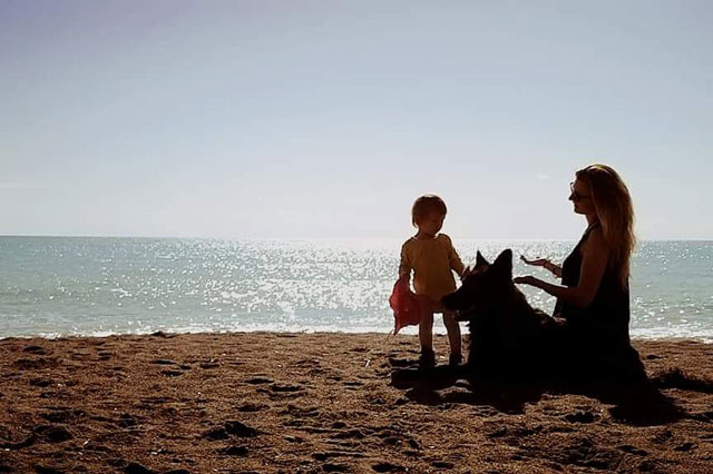 Hund mit Baby und Mutter am Strand